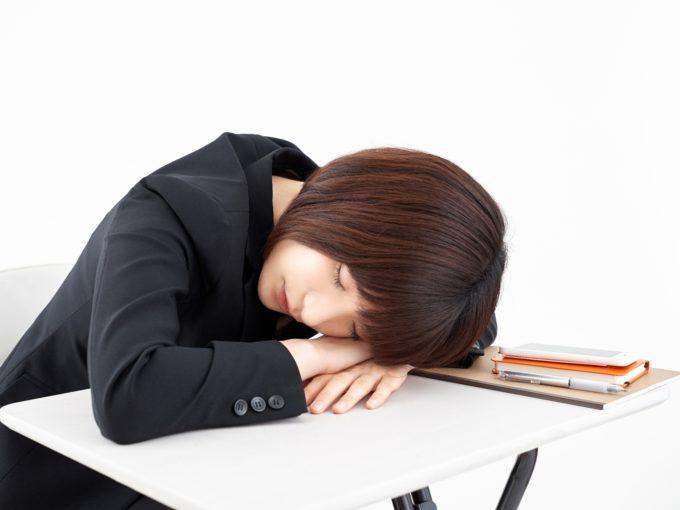 白背景で昼寝をする女性
