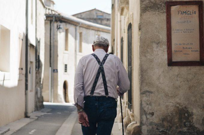 杖をついて歩く男性