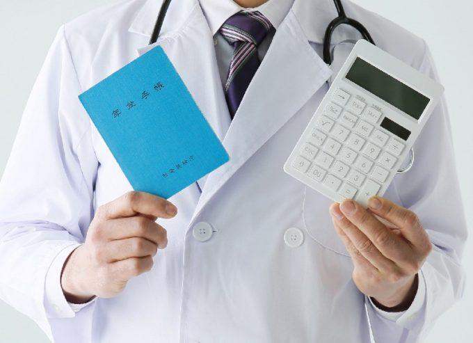 年金手帳と電卓を持つ医者
