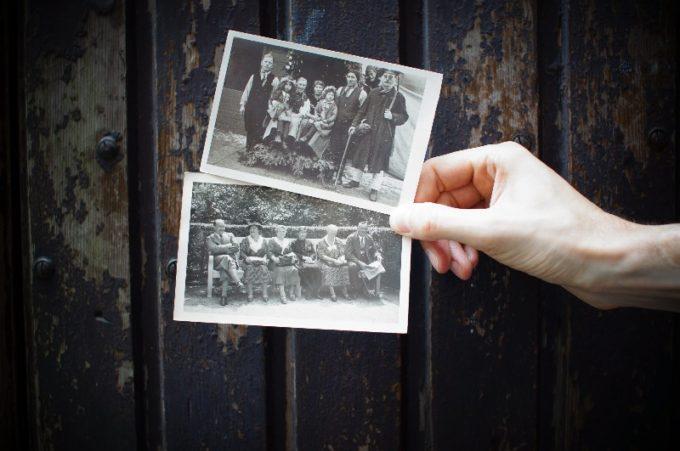 古い2枚の写真を手に持つ人