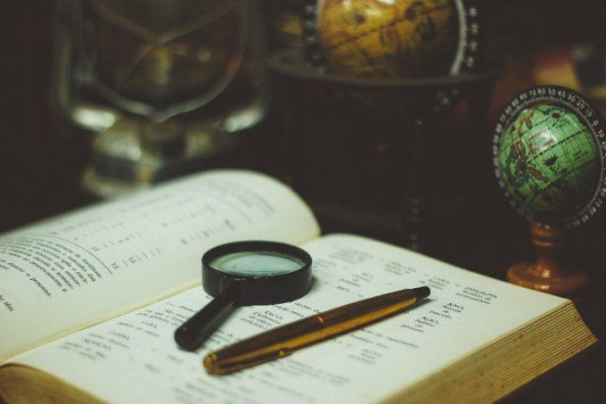 ページの開いた本の上に置かれた虫眼鏡とペン